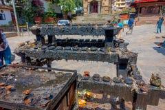 加德满都,尼泊尔2017年10月15日:走接近有熔化candels的一个黑暗的金属盘子的未认出的人民在 库存图片