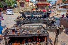加德满都,尼泊尔2017年10月15日:走接近有熔化candels的一个黑暗的金属盘子的未认出的人民在 免版税图库摄影