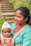 加德满都,尼泊尔- 2016年11月04日:运载她的婴孩的年轻尼泊尔母亲在村庄,尼泊尔 免版税库存图片