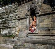 加德满都,尼泊尔- 2016年9月21日:一个圣洁Sadhu人的画象有被绘的面孔的在Pashupatinath寺庙在加德满都,尼泊尔 免版税库存照片