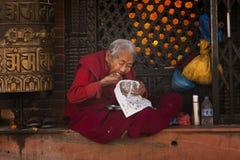 加德满都,尼泊尔cirka 2017年11月:吃在寺庙前面的一个和尚一顿膳食 库存照片