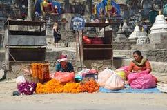 加德满都,尼泊尔, 2013年10月, 10日,尼泊尔场面:妇女在加德满都卖在街道上的礼节花 库存照片