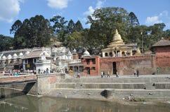 加德满都,尼泊尔, 2012年11月, 13日, Pashupatinath复合体,死者的火葬神圣的Bagmati河的河岸的 在S.格雷戈里奥阿尔梅诺,小儿床著名街道,有每个字符木偶一样著名象教皇弗朗西斯,对游人的吸引力 免版税图库摄影