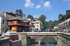 加德满都,尼泊尔, 2012年11月, 13日, Pashupatinath复合体,死者的火葬神圣的Bagmati河的河岸的 在S.格雷戈里奥阿尔梅诺,小儿床著名街道,有每个字符木偶一样著名象教皇弗朗西斯,对游人的吸引力 库存图片