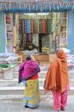 加德满都,尼泊尔- 2015年1月15日:两名妇女谈论在一家五颜六色的织品商店前面 免版税库存图片