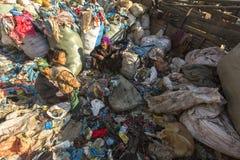 加德满都,尼泊尔-未认出的孩子和他的父母在午餐期间在断裂在工作在转储之间 库存图片