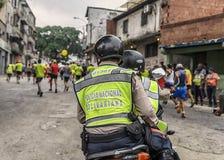 加拉加斯,委内瑞拉- 2016年4月24日:维持照料治安马拉松运动员在CAF马拉松42K 库存照片