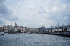 加拉塔塔区,大厦,有钓鱼的人和博斯普鲁斯海峡海水的桥梁晚上视图与小船、海鸥和云彩 图库摄影