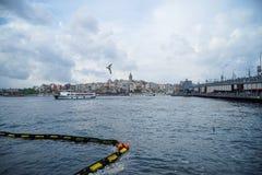 加拉塔塔区,有钓鱼的人和博斯普鲁斯海峡海水的桥梁晚上视图与小船、浮体、海鸥和多云天空 免版税库存图片