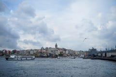 加拉塔塔区,有钓鱼的人和博斯普鲁斯海峡海水的桥梁晚上视图与小船、海鸥和多云天空 库存图片