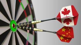 加拿大和中国的旗子击中目标的舷窗的箭的 概念性的国际合作或的竞争 股票视频
