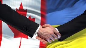 加拿大和乌克兰握手国际友谊联系,旗子背景 股票视频