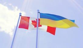 加拿大和乌克兰,挥动反对蓝天的旗子 库存图片