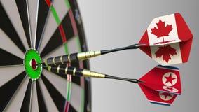 加拿大和北朝鲜的旗子击中目标的舷窗的箭的 国际合作或竞争 股票录像