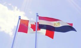 加拿大和埃及,挥动反对蓝天的旗子 库存图片