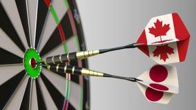 加拿大和日本的旗子击中目标的舷窗的箭的 概念性的国际合作或的竞争 影视素材