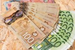 加拿大和欧洲金钱有木背景 免版税库存照片