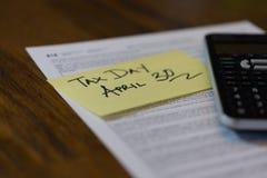 加拿大税天从与计算器和稠粘的笔记的4月30日税 库存图片