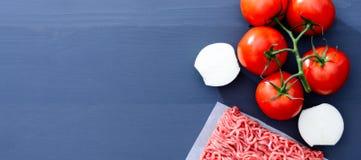 加料碎肉用在一棵分支和切的葱的红色蕃茄在与拷贝空间的灰色木背景 免版税库存图片