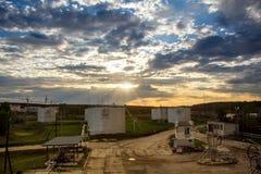 加油的飞机的燃料贮存坦克在日落背景 库存照片