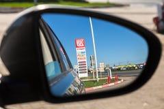 加油站卢克石油价格在后视镜的标志反射 免版税库存图片