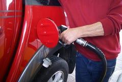 加油车的一个人的手拿着燃油泵喷管 免版税库存图片