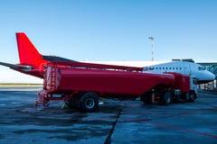 加油飞机的红色罐车停放对搭乘桥梁在机场围裙 免版税库存图片