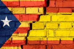 加泰罗尼亚语和西班牙的旗子在砖墙上有大裂缝的在中部 问题的标志在国家之间的 库存图片