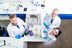 加满三位研究员实验室队与反应剂a一起使用 图库摄影