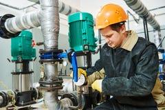 加热系统的技术员水管工在锅炉室 免版税库存图片
