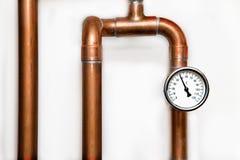 加热系统` s木桶匠用管道输送与在白色墙壁上的温度计 免版税库存照片