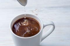 加牛奶到一杯咖啡 免版税库存照片