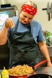 加盐的女性厨师到在红色平底锅的三文鱼和鲕梨混合 库存照片