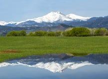 加盖的雪在一个春日渴望高峰反射在水域中 库存照片