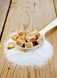 加糖在一把匙子的棕色和砂糖在委员会 图库摄影