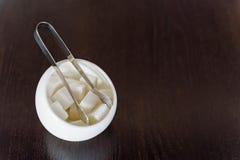 加糖在糖罐和糖钳子的立方体 库存图片