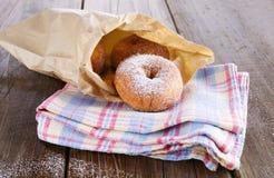 加糖在纸袋的搽粉的桂香多福饼在土气木背景 免版税库存照片