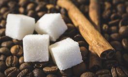 加糖立方体和两根肉桂条用咖啡豆 免版税库存照片
