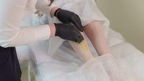 加糖脚的去壳在美容院的 使用糖酱的头发撤除 股票录像