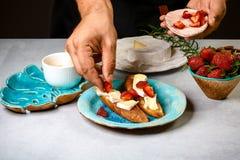 加草莓到bruschetta三明治由厨师手 准备食物的烹饪过程 免版税库存照片