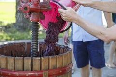 加葡萄到一台老木手工葡萄压榨机 库存图片