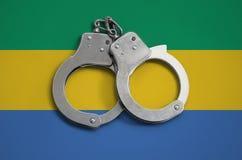 加蓬旗子和警察手铐 法律在国家和保护的遵守的概念免受罪行 库存图片