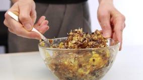 加蜂蜜到坚果黄油和混合在碗的妇女成份 股票视频