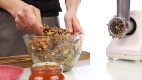 加蜂蜜到坚果黄油和混合在碗的妇女成份 股票录像