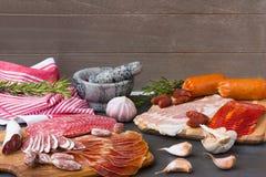 加调料的口利左香肠、jamon和其他西班牙肉开胃菜在黑木背景用香料 免版税库存照片