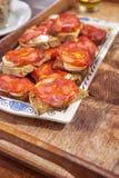 加调料的口利左香肠和山羊乳干酪多士在瓷板材在木 库存图片