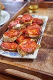 加调料的口利左香肠和山羊乳干酪多士在瓷板材在木 免版税库存图片