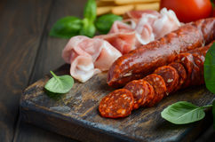 加调料的口利左香肠香肠 西班牙传统加调料的口利左香肠香肠和火腿用新鲜的草本和蕃茄 库存图片