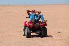 洪加达,埃及- 2015年4月24日:一个年轻埃及人在方形字体,埃及,洪加达的沙漠徒步旅行队以后休息说谎在他的ATV 库存照片