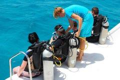 洪加达,埃及- 2015年4月30日:妇女潜水教练作指示初学者在潜水从小船前,红海,埃及 库存照片